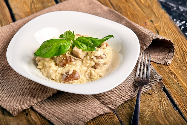 Homemade traditional italian mushroom risotto on wooden table