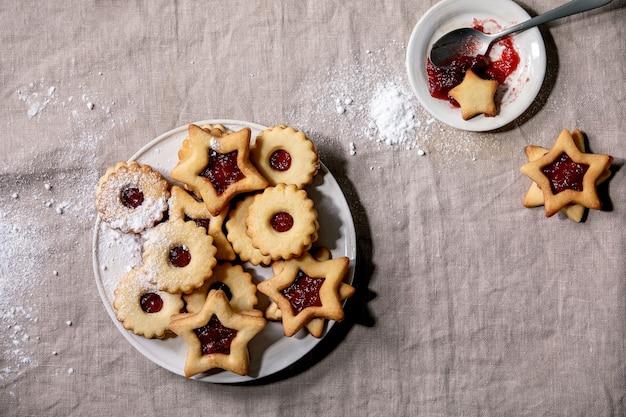 リネンのテーブルクロスの上のセラミックプレートに赤いジャムと粉砂糖を添えた自家製の伝統的なリンツショートブレッドビスケットクッキー。フラットレイ、スペース