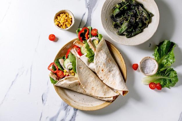 白い大理石の表面に焼きピーマン、ハラペーニョ、トウモロコシ、塩を添えた、セラミック プレートに豚肉と野菜を入れた自家製の伝統的なメキシコ トルティラ ラップ。平面図、フラット レイアウト。