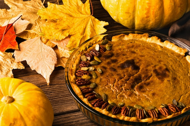 Homemade traditional pumpkin pie decorated with nuts and seeds. natural rustic style wooden background.