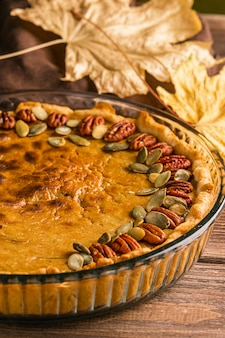 Homemade traditional pumpkin pie decorated with nuts seeds. natural rustic style wooden background.