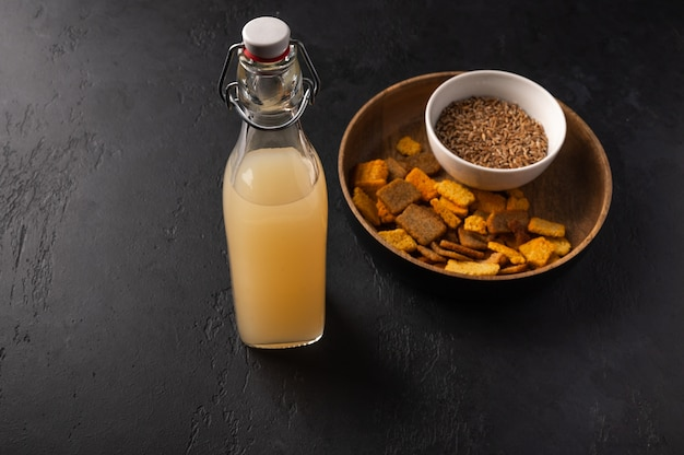 ボトルと暗い木製のクラッカーで自家製の伝統的なロシアの軽いライ麦kvass