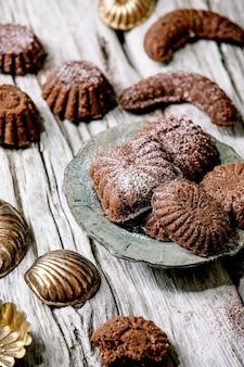 古い木の表面にクッキーの型が付いたセラミックプレートにココア粉砂糖を入れた自家製の伝統的なショートクラストクッキーチョコレートクレセント。フラットレイ、スペース