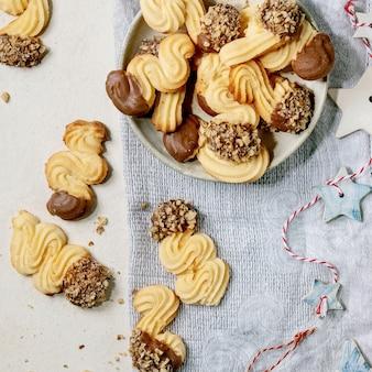 自家製の伝統的なショートクラストクッキーは、チョコレートの釉薬とナッツでさまざまな形をしています。白い背景の上にクリスマスの星の装飾が施されたセラミックプレート。フラットレイ、コピースペース