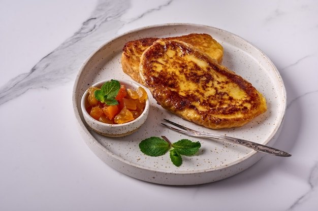 Homemade traditional spanish torrijas or french toast with melon candied fruit and mint