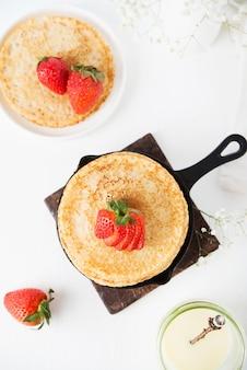 흰색 표면에 딸기와 함께 만든 전통적인 얇은 팬케이크, 평면도