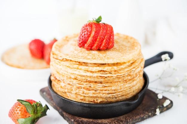 흰색 표면에 딸기와 함께 만든 전통적인 얇은 팬케이크