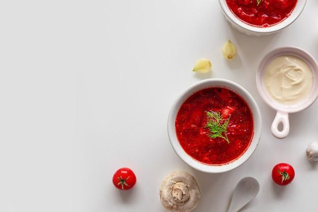 Домашний традиционный украинский свекольный суп со свежим зеленым укропом. русский борщ в миске помидоров, сметаны и грибов на белом фоне с копией пространства.