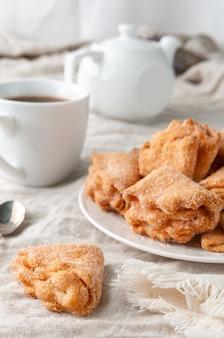 砂糖をまぶした凝乳フィリングを使った自家製の三角クッキー。白いお皿に。背景グレーのリネン。奥にはかつてのティーポットとカップ。