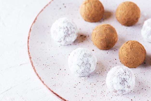 코코넛 밀크와 코코아 가루를 넣은 홈메이드 트러플을 가벼운 접시에 담은 설탕 글루텐과 유당 없음