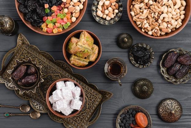 Домашняя турецкая сладость пахлава; даты; сухофрукты и орехи на металлической и глиняной миске над столом