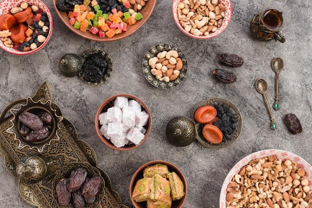 콘크리트 배경에 숟가락으로 말린 과일과 견과류로 만든 터키어 기쁨 과자