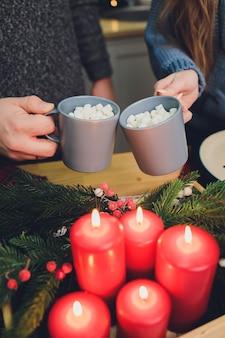 Самодельные два бокала какао с зефиром. горячий зимний напиток на деревянном фоне, украшенный палочками корицы и еловыми ветками.