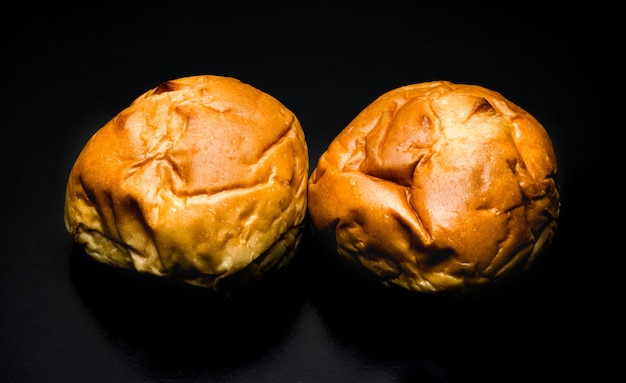 Homemade two delicious burger buns on a textured dark background