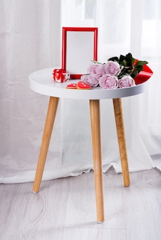 Homemade valentines day heart cookies, pink roses and red frame on white table near floor