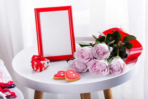 Homemade valentines day heart cookies, pink roses and red frame on white table