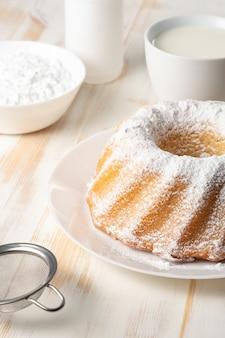 白い木製の背景に自家製バニラバントケーキ。