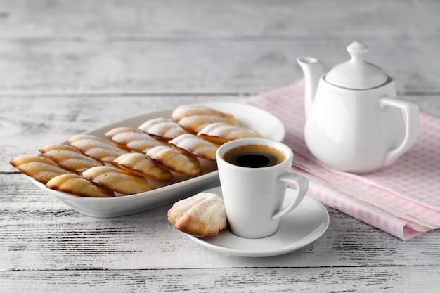 木製の背景にコーヒーのカップと自家製バニラcookieswith