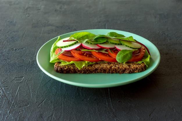 토마토, 래튜스 무, 오이, 파를 곁들인 홈메이드 비건 및 채식 샌드위치. 건강한 아침 식사.