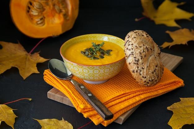 種とパンが入った自家製ビーガンパンプキンクリームスープ。黒の背景に黄色のカエデの葉。