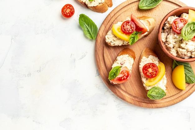Домашний веганский бутерброд с помидорами, сливочным сыром и листьями базилика. здоровая еда, крупный план сэндвича томата диеты.