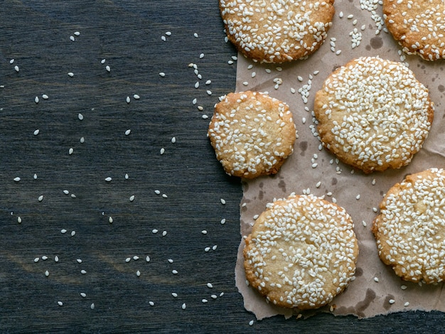 Homemade vegan tahini cookies are laid out on a dark table
