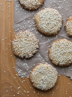 Homemade vegan tahini cookies are laid out on a wooden table
