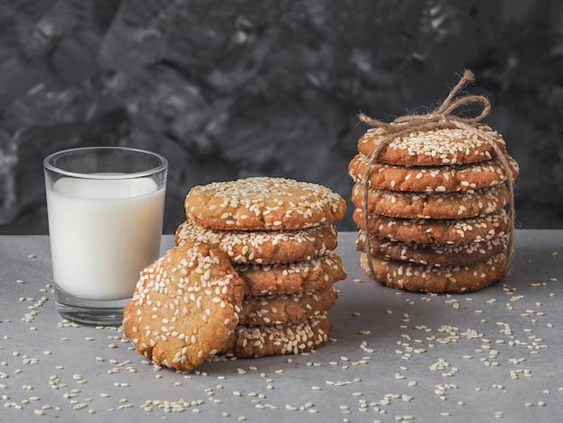 Homemade vegan tahini cookies in stack with glass of milk