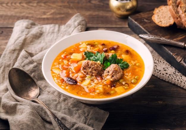 Домашний овощной суп с фрикадельками и ломтиками хлеба на деревенском деревянном
