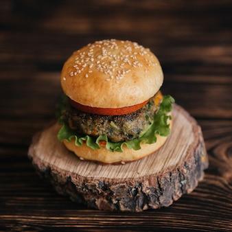 Домашний вегетарианский бургер на деревянной подставке крупным планом