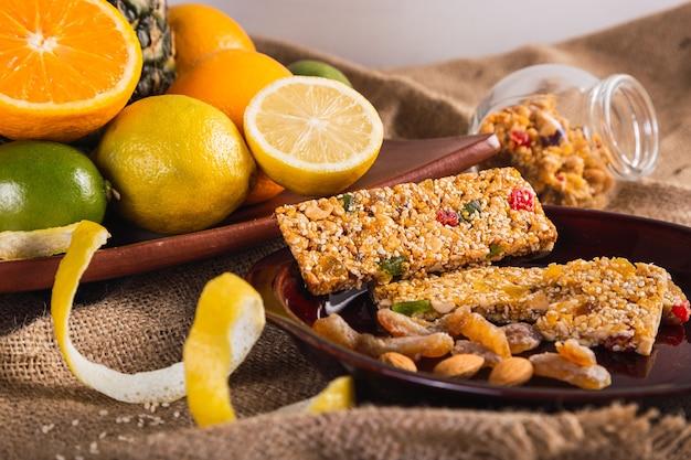 素朴な背景にオレンジ、レモン、種子、蜂蜜を使った自家製のベジタリアングラノラバー-健康的な食事のための柑橘系の果物、蜂蜜、ゴマを使ったシリアルバー。