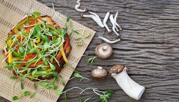 木製のテーブルの背景にヒマワリの芽とキノコの自家製ベジタリアンピザ