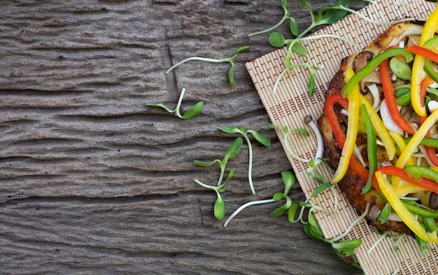 木製のテーブルの背景にひまわりの芽と自家製ベジタリアンピザ