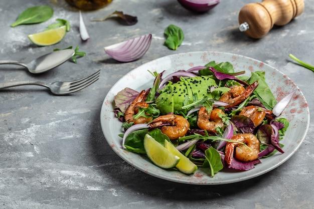 Домашний вегетарианский салат из креветок с авокадо, луком и смешанными листьями. здоровая пища. чистая еда. место для текста, вид сверху.