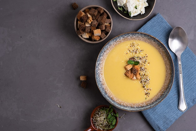 Homemade vegetarian squash cream soup with croutons and microgreens, healthy food concept, copy space.
