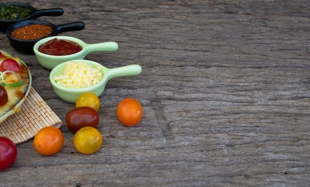 체리 토마토와 나무 배경에 다른 재료로 만든 야채 피자