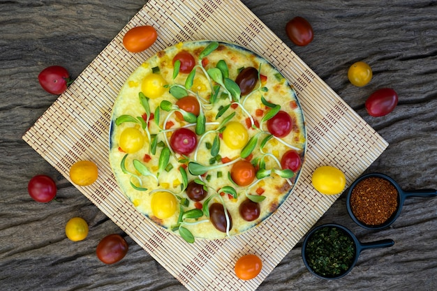 Homemade veggie pizza with cherry tomatoes and other ingredients on a wooden background