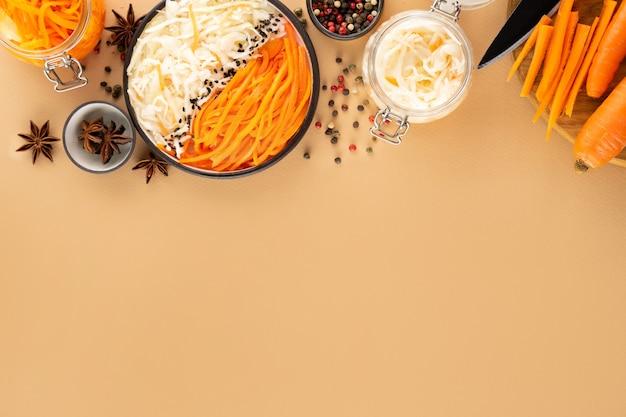 수제마을 발효 김치와 당근. 스타 아니 스, 검은 색과 붉은 고추. 세라믹 그릇에 채식주의 샐러드입니다. probiotics 창자 건강 개념입니다. 창조적 인 베이지 색 배경에 슈퍼 푸드, 복사 공간.
