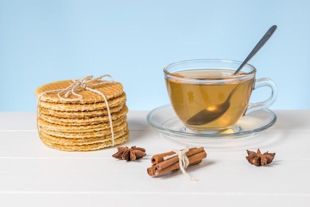 파란색 배경에 흰색 테이블에 유리 컵에 집에서 만든 와플과 차. 차와 함께 만든 수제 케이크.