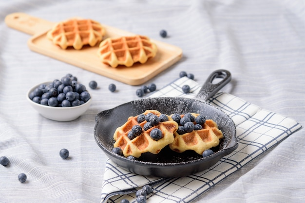 Homemade waffles blueberries and icing on a dish that looks like a pan.