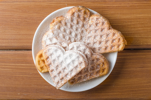 Homemade waffles heart sprinkled with powdered sugar on plate on a wooden table.