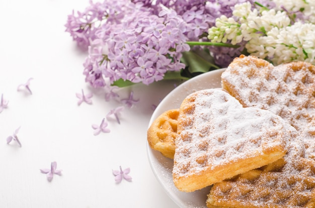 Homemade waffles heart sprinkled with powdered sugar