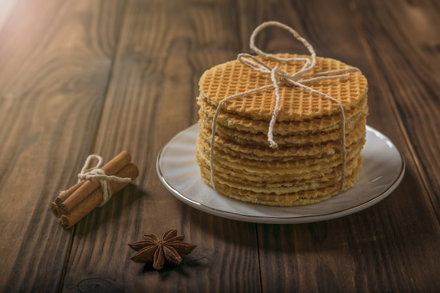 나무 테이블에 레몬과 계피를 넣은 끈으로 묶인 홈메이드 와플. 향신료로 만든 수제 케이크.