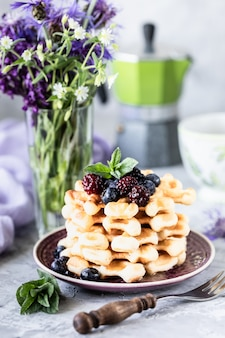 Homemade waffles with berries and honey, a cup of coffee on the table with a bouquet of lilacs.