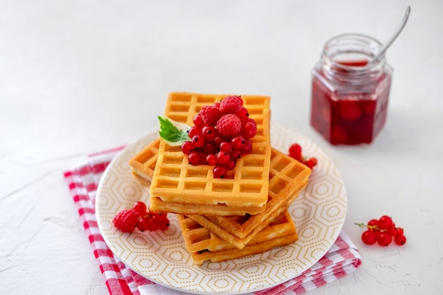 Homemade waffles with berry and jam