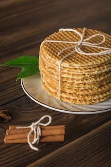 나무 테이블에 카라멜 크림과 계피 스틱을 넣은 홈메이드 와플. 향신료로 만든 수제 케이크.
