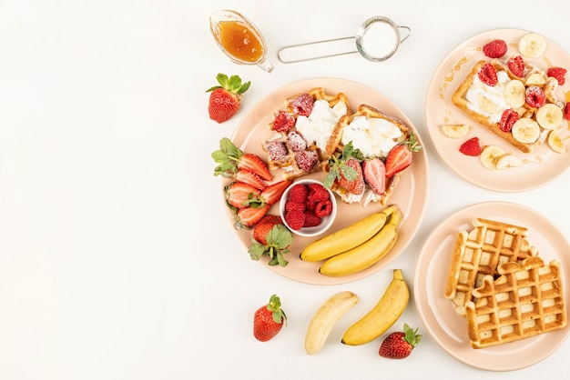 Homemade waffles with fruits and berries, cream and honey in a plate on white table. flat lay, top view, copy space.