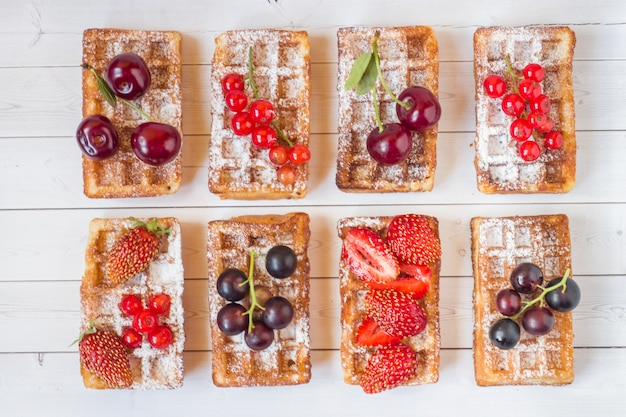 Homemade waffles with summer berries on a light table. selective focus