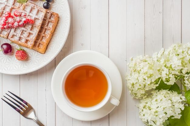 皿の上の夏の果実と自家製ワッフル。ライトテーブルの上の紅茶のカップ。セレクティブフォーカス
