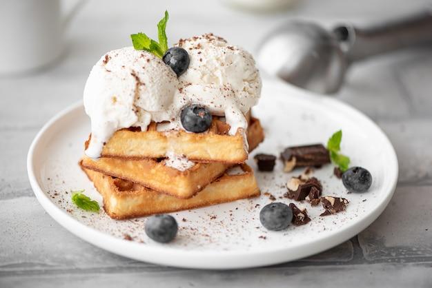 白い皿にアイスクリームとチョコレートの2つのスクープの自家製ワッフル